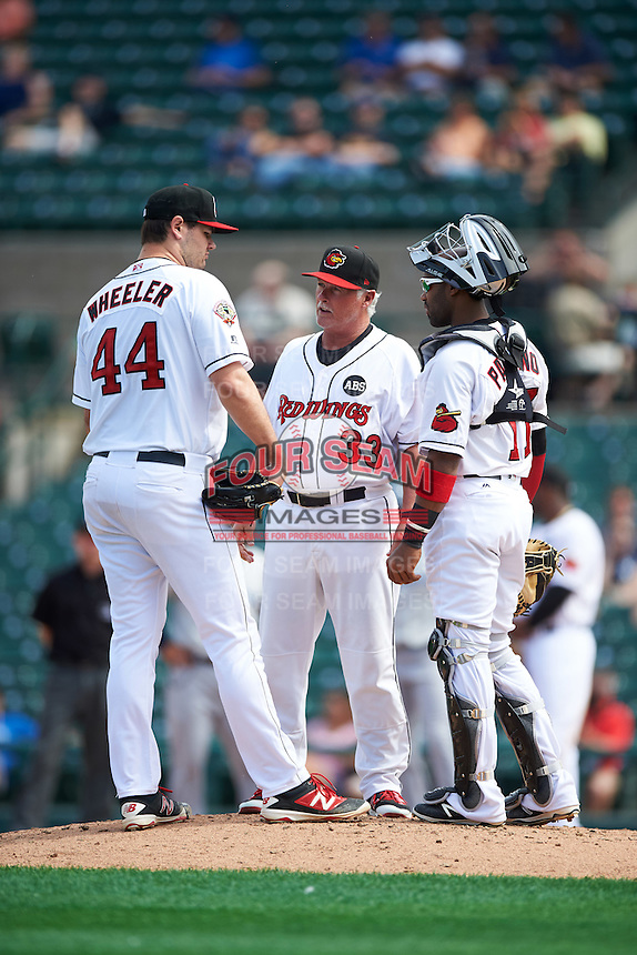 Rochester Red Wings pitching coach Stu Cliburn (33) talks with pitcher Jason Wheeler (44) and catcher Carlos Paulino (17) during a game against the Columbus Clippers on June 16, 2016 at Frontier Field in Rochester, New York.  Rochester defeated Columbus 6-2.  (Mike Janes/Four Seam Images)