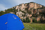 A tent on a hill along the Smith River in Montana with a view of a rock wall across the river