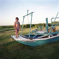 Kirstin Guidry stands on the front of her grandfather's skiff on the lawn of their house on Isle Jean Charles, Louisiana. The island is clinging to life after decades of severe erosion of coastal marshes that once provided a buffer against hurricanes and high tides.  Only 70 or so residents remain, down from 300 at its peak. The predominantly Native American community has battled for autonomy and land rights for generations. Members of the community were banned from attending integrated schools with white residents until the early 1970s, while at the same time coastal Louisiana tribes continue to be denied Native American recognition that would grant benefits under US federal law.