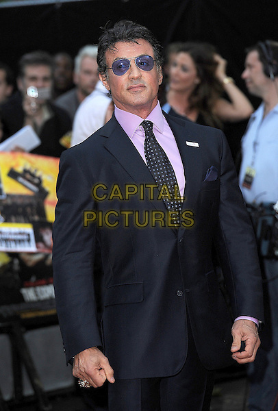 "SYLVESTER STALLONE.""The Expendables"" UK Film Premiere, Odeon Leicester Square, London, England..August 9th, 2010.half length black suit pink shirt sly purple tie navy blue tinted glasses sunglasses shades .CAP/BEL.©Tom Belcher/Capital Pictures."