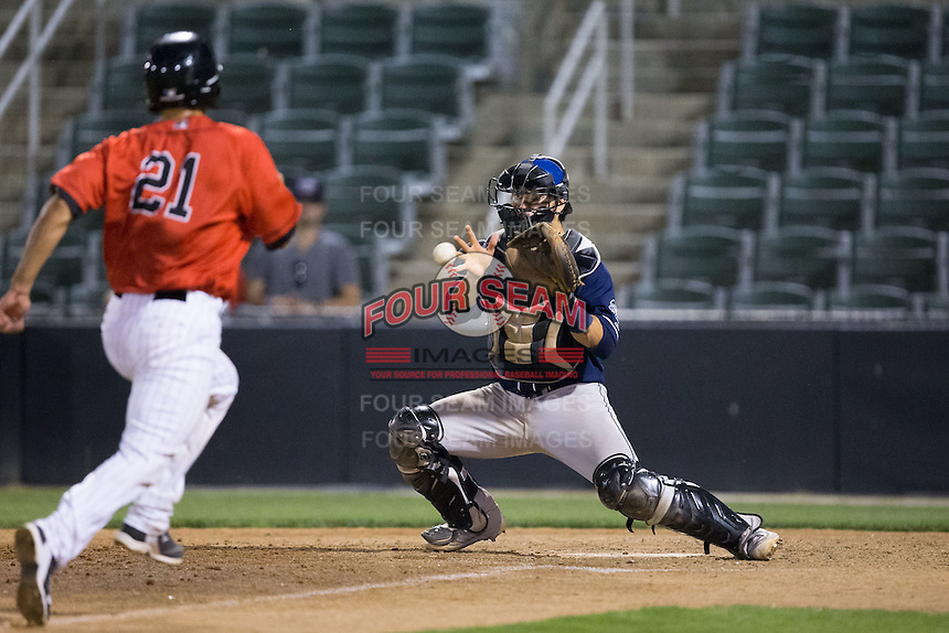 Asheville Tourists catcher Chris Rabago (22) waits for a throw as Seby Zavala (21) of the Kannapolis Intimidators hustles towards home plate at Kannapolis Intimidators Stadium on May 26, 2016 in Kannapolis, North Carolina.  The Tourists defeated the Intimidators 9-6 in 11 innings.  (Brian Westerholt/Four Seam Images)