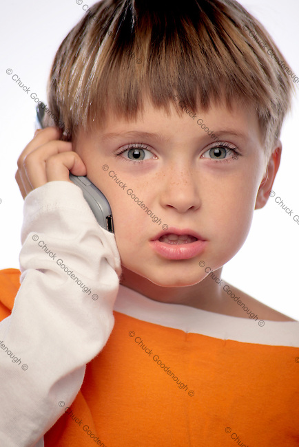 Photo of a little boy talking on a cellphone. He's in the middle of a sentence and looking straight at camera.