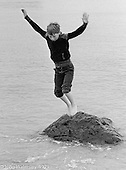 Leaping from a rock.  One of the kids from Wester Hailes taken by Youth Workers on a visit to the beach near Dunbar, East Lothian, Scotland, 1979.  John Walmsley was Photographer in Residence at the Education Centre for three weeks in 1979.  The Education Centre was, at the time, Scotland's largest purpose built community High School open all day every day for all ages from primary to adults.  The town of Wester Hailes, a few miles to the south west of Edinburgh, was built in the early 1970s mostly of blocks of flats and high rises.