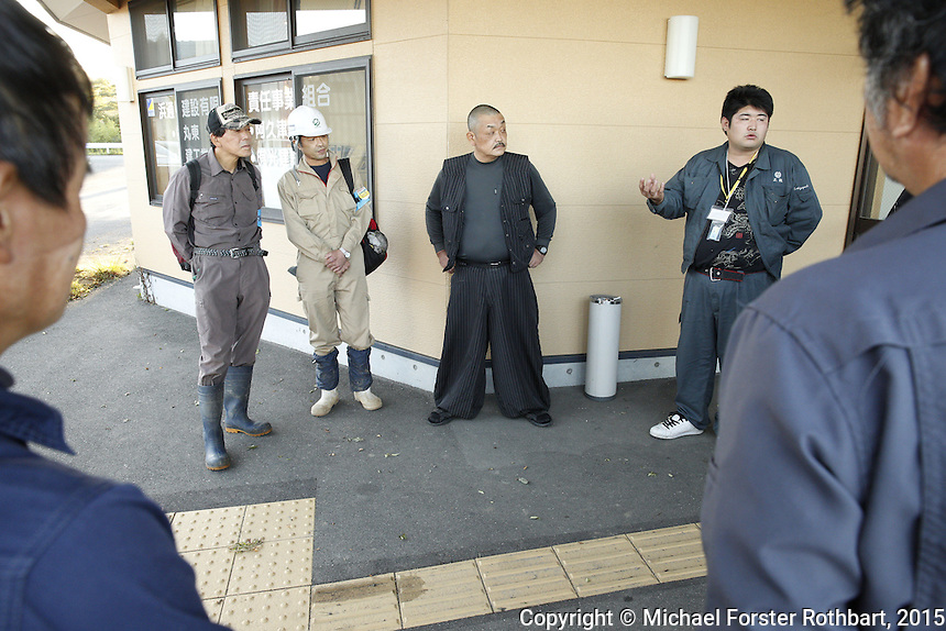 Decontamination laborers employed by the Maruto construction company meet outside the company&rsquo;s office in Tomioka, Japan, to report on their progress at the end of the day. In 2015, four and a half years after the Fukushima Daiichi nuclear power plant disaster, workers are decontaminating homes and commercial properties. Almost all developed properties in Tomioka are now getting cleaned or demolished. Full caption to come.<br /> <br /> &copy; Michael Forster Rothbart Photography<br /> www.mfrphoto.com &bull; 607-267-4893<br /> 34 Spruce St, Oneonta, NY 13820<br /> 86 Three Mile Pond Rd, Vassalboro, ME 04989<br /> info@mfrphoto.com<br /> Photo by: Michael Forster Rothbart<br /> Date:  10/2/2015<br /> File#:  Canon &mdash; Canon EOS 5D Mark III digital camera frame B19397
