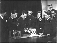 BNPS.co.uk (01202 558833).Pic: StewartWardrope/BNPS..***Please use full byline***..Aircrews being trained by a SPS operative in the correct deployment of the plucky birds....Valuable bravery medals awarded to a flock of wartime homing pigeons have come to light to reveal the ingenious ways the British went about spying on the enemy...The birds were strapped in mini-parachutes and placed in small crates that were dropped behind enemy lines in order for the French Resistance to use...A corkscrew fan on the wooden crate unwound in the wind leading to the door to open.automatically in mid-air, allowing the pigeon to drop to the ground...The French attached coded messages about German military movements to the birds which flew across the English Channel with the precious intelligence...But one chilling note that has emerged after 70 years was written in German and informed the British the French recipient had been shot for spying having been found with a pigeon...Some 32 racing pigeons were awarded the prestigious Dickin Medal - the animal version of the Victoria Cross - for their acts of heroism in World War Two...The Royal Pigeon Racing Association owns five of them. Its general manager, Stewart Wardrope, took them along to the BBC's Antiques Roadshow to show them off...He also revealed the stories behind their award as well some of the other madcap inventions made by British boffins and used to gather intelligence using the birds...These included a clockwork camera strapped to the belly of a pigeon that automatically took reconaissance snaps of Nazi-occupied Europe before returning home...Of the five medals due to be featured on this Sunday's Antiques Roadshow, two were awarded to pigeons that delivered important intelligence from Europe six times between them...Another, named 'Beachcomber', brought back the first news of the disastrous landings at Dieppe in September 1942.