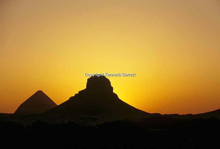 Dashur; Egypt, The sun sets behind the core of 12th dynasty Middle Kingom Pharaoh Amenenhet III, and the Bent pyramid of 4th dynasty ruler Snefru