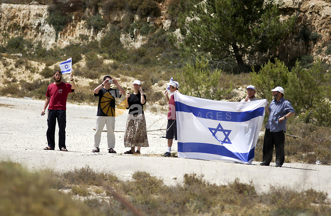 Israeli settlers hold up Israeli flag as Palestinians from the village of Bet In, north of Ramallah protest against Israeli occupation on June 11, 2010 near the Jewish settlement of Beit El. Photo by Eyad Jadallah