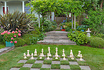 Vashon-Maury Island, WA: Oversized chess board in a lawn in a cottage garden featuring bright pink geraniums, wisteria trellis, phormium, and ferns