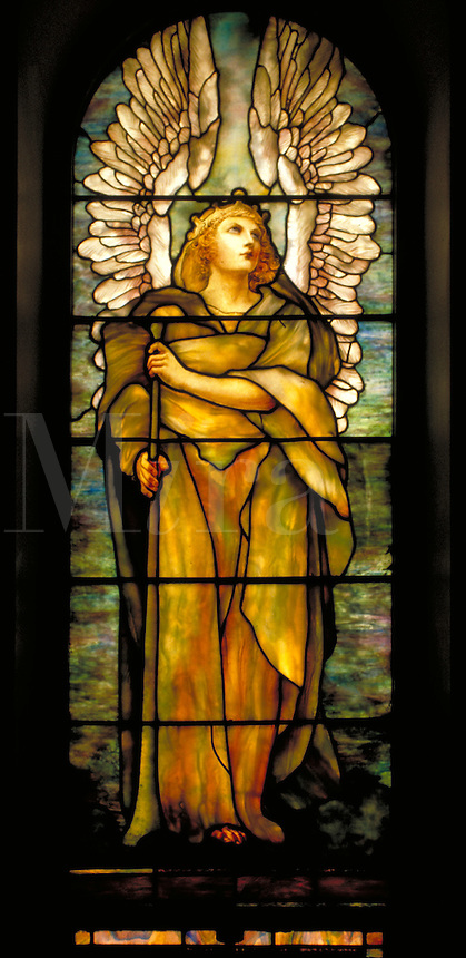This stained glass window depicting a winged golden angel adds warm light and color to the peaceful atmosphere of the Erskine and American Church in Montreal, Canada. Montreal, Canada Erskine and American Church.