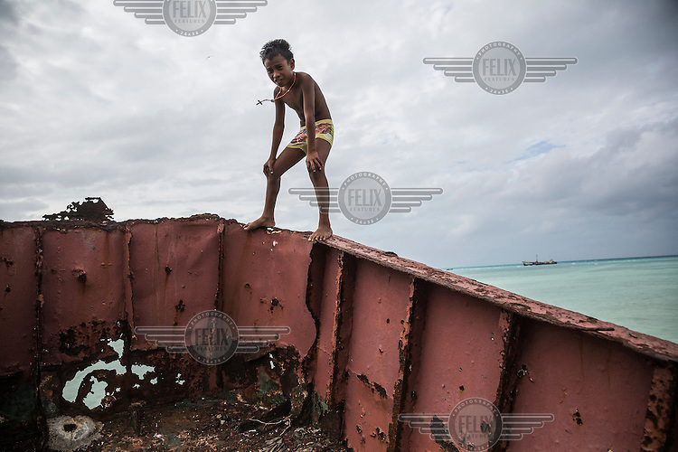 Tawati, seven, stands on the rusting remains of a wrecked ship which was lifted and smashed onto the town's sea wall during a king tide in February 2015.