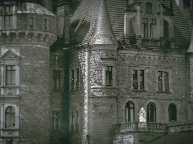 A dream image of an old castle, with a small figure of a veiled ghostly woman  standing on a balcony.