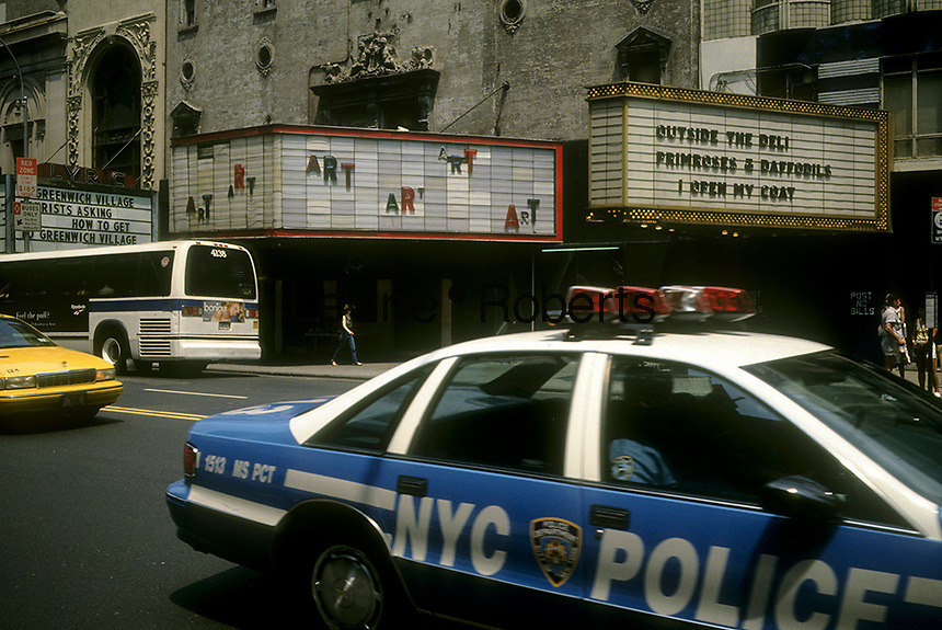 Theaters, including the Victory Theatre, center, on West 42nd Street between Seventh and Eighth Avenues in Times Square in June 1994. The marquees of the empty theaters hosted a public art exhibit. (© Richard B. Levine)