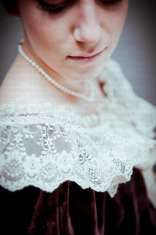 Young woman with short brown hair wearing period dress with lace collar and pearl necklace