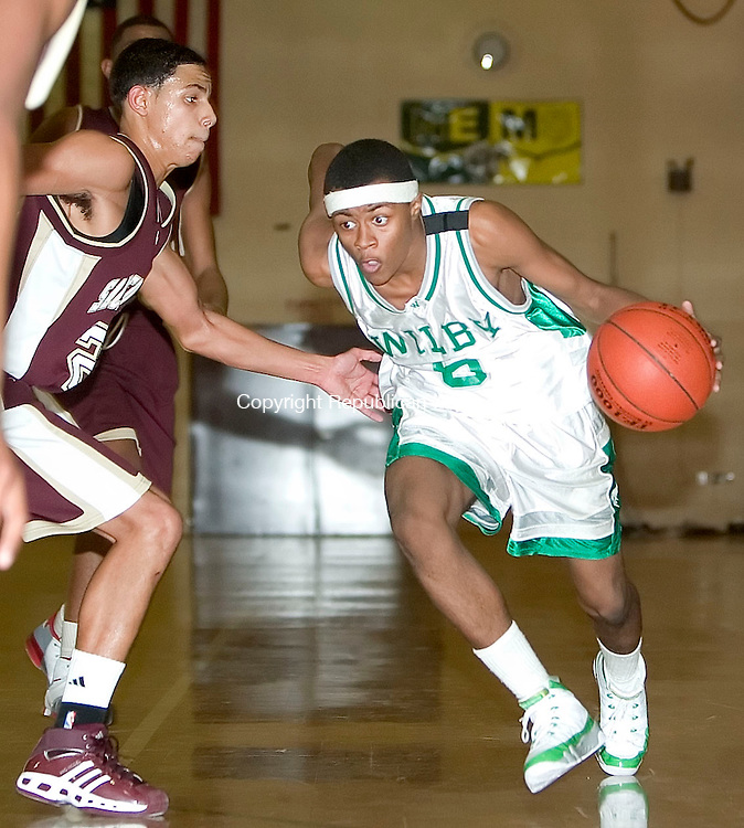 WATERBURY, CT- 15 DEC 06- 121506JT14- <br /> Wilby's Lashawn Yates dribbles past Sacred Heart's Bryant Corcoran at Friday's game at Wilby. Sacred Heart won 68-65.<br /> Josalee Thrift Republican-American