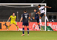 LAKE BUENA VISTA, FL - JULY 26: Theo Bair of Vancouver Whitecaps FC and Roberto Puncec of Sporting KC challenge for a header in the box as Tim Melia of Sporting KC looks on during a game between Vancouver Whitecaps and Sporting Kansas City at ESPN Wide World of Sports on July 26, 2020 in Lake Buena Vista, Florida.
