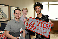 Members holding a banner for the TKE Educational Foundation.