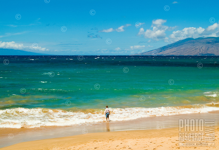 "A swimmer stands at the edge of """"Baby or Little Beach"""" at Makena. West Maui mountains in background."