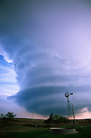 The striated updraft of a supercell thunderstorm looms above a windmill in Western Oklahoma in April. This storm produced hail to the size of baseballs.