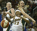 Seattle Storm's Betty Lennox (22) gets the ball knocked away by New York Liberty's Kelly Schumacher in second half action Friday, July 14, 2006 at Key Arena in Seattle. Storm's Lauren Jackson, left, tries to block Schumacher out of the play while Liberty's Shameka Christon, right, helps Schumacher. The Storm beat the Liberty 86-66. (AP Photo/Jim Bryant)
