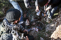 In this Saturday, Dec. 15, 2012 photo, a lifeless body of one pro-government soldier lays inside a trench as Syrian rebel fighters look for his identity after kill him during heavy clashes inside one militar academy besieged by rebels at the north of Aleppo, Syria. The Free Syrian Army took control over the Academy after several hours battling the troops loyal to President Bashar al-Assad. Among the casualities are one FSA General and one Syrian journalist. (AP Photo/Narciso Contreras)