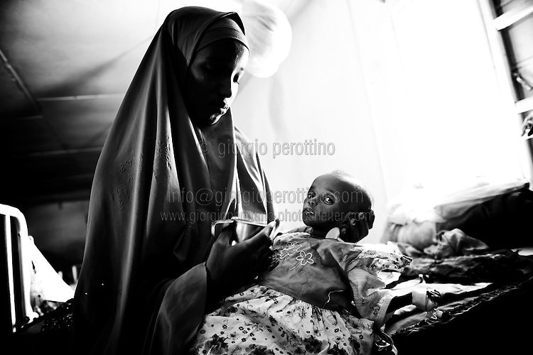 Malnutrition in the Horn of Africa.<br /> <br /> A mother feeds her denutrition-affected daughter with some milk at the pediatric and malnutrition branch of the hospital of Hargeisa, the capital city of Somaliland in the Horn of Africa.<br /> The Northern region of former Somalia Republic reached its independence from the southern part in 1988 after a long period of civil war, but it is not actually recognized by any international country and community.     <br /> Hargeisa, Somaliland - 07th Aug 2011<br /> © Giorgio Perottino