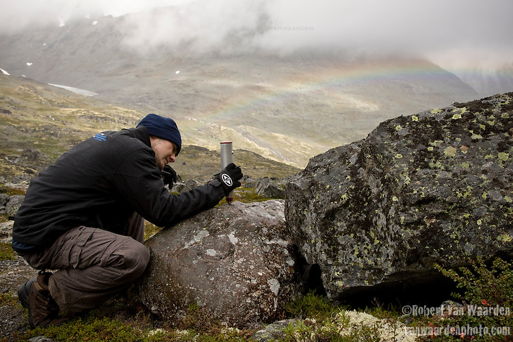 Below the Storbrean, high in the mountains of Norway's Jotunheimen Nasjonalpark, Robert Way conducts a Schmidt Hammer test on a glacial moraine. The test will measure rock hardness and these measurements, will help Mr. Way determine the weathering on the rock and subsequently  determine when this moraine was formed.  Robert Way is a University of Ottawa student on exchange to the University of Oslo on a geography program.