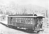#9 baggage &amp; coach combine possibly in Marshall Pass.  Man, woman and boy in turn of century clothing on back of cars.  Hand hewn railroad ties.<br /> D&amp;RGW