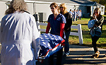 WOLCOTT, CT-101117JS04-- Debra Agosto Threlfall, looks on as staff from the Wolcott Veterinary Clinic carry the flag draped box containing Lily, a 17-year old retired state police narcotics dog, to a waiting vehicle on Thursday after the family chose to have her put to sleep due to health issues. Woloctt police gave the family a police escort to the clinic and back home. <br /> Jim Shannon Republican-American
