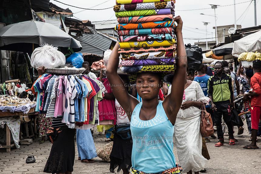 Mercato di Cotonou, ragazza trasporta tessuti,