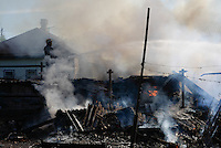 Fire fighters exstinguish houses on flames destroyed by shelling. Slovyansk. Ukraine.