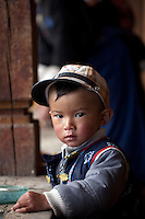 "May 1st, 2011_Shangri-La, Yunnan, China_ Two year old Nima Qeling looks on shyly from his traditional Tibetan farmhouse, in the tiny village of Rime, near the town of Zhongdian (or Shangri-La) in northern Yunnan province, China.  This family is one of several local families taking advantage of ""Home Stays,"" by opening their homes to visiting tourists.  Photographer: Daniel J. Groshong/The Hummingfish Foundation"