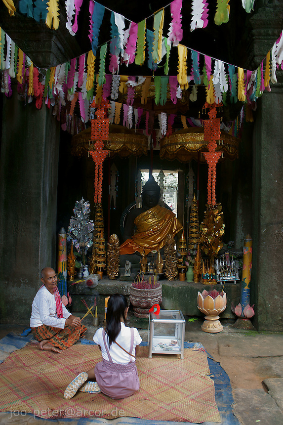 child praying in front of buddha shrine in Bantheay Kdei Temple,   Angkor Wat, Cambodia, August 2011