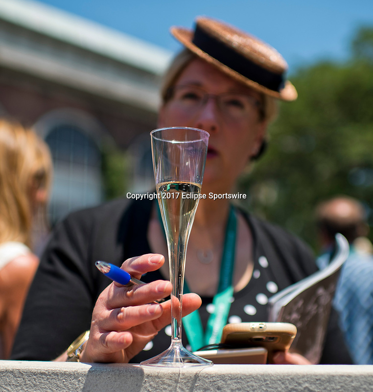 ELMONT, NY - JUNE 10: A woman enjoys a glass of champagne while she handicaps a race on Belmont Stakes Day at Belmont Park on June 10, 2017 in Elmont, New York (Photo by Scott Serio/Eclipse Sportswire/Getty Images)