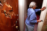 "Beatrice Turner, 89, stands with the .22 caliber pistol she used to fend off an intruder who broke down her front door, left, in the early morning hours.  Turner, who did not want her face shown in this photograph, emerged from her bedroom at rear, fired one shot and missed, then calmed the intruder who was then arrested by Des Moines Police officers who arrived at her northeast Des Moines home.  ""About six officers were here, and they reloaded the gun for me,"" she said.  ""All of them were hugging me and telling me how brave I was."""