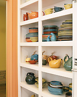 In the kitchen stacks of brightly coloured crockery are housed on practical open shelves
