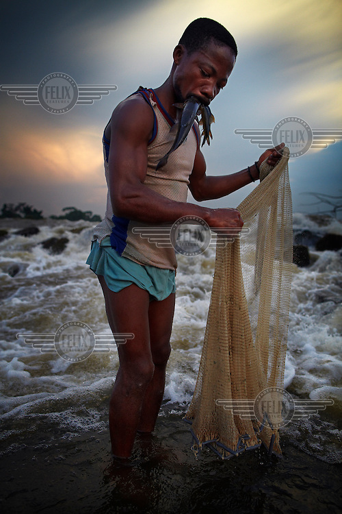 A fisherman holds fish in his mouth to keep his hands free to cast a net at at Boyoma Falls (known locally as Wagenia Falls) on the Congo River..