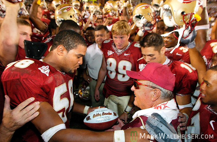 After Florida State's defeat of Wake Forest in Tallahassee on October 25, 2003, FSU linebacker Michael Boulware (L) presents a commemorative football to Florida State head coach Bobby Bowden stating that Bowden became the winningest living football coach and the coach with the most wins in Division 1 with 339 -- passing Joe Paterno. Quarterback Chris Rix (16) is in the background as the rest of the team with helmets raised in a team chant.