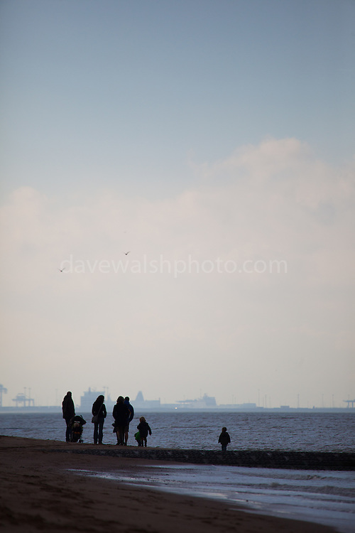 People on the beach at Knokke, Flanders, Belgium, with the port of Zeebrugge in the background.