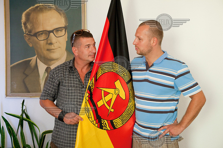 """Daniel Helbig (right) and Guido Sand were performers in the East German State Circus and now co-own the DDR Ostel in Berlin which tries to recreate an atmosphere similar to that in East Germany before the fall of the Berlin Wall. They pose in their office with a portrait of Erich Honecker, former East German president, and the flag of the DDR (East Germany) as part of the """"commie-kitsch"""" asthetic of the hostel."""