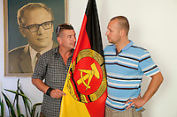 "Daniel Helbig (right) and Guido Sand were performers in the East German State Circus and now co-own the DDR Ostel in Berlin which tries to recreate an atmosphere similar to that in East Germany before the fall of the Berlin Wall. They pose in their office with a portrait of Erich Honecker, former East German president, and the flag of the DDR (East Germany) as part of the ""commie-kitsch"" asthetic of the hostel."