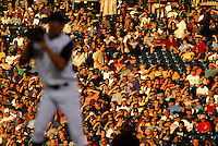 12 August 08: Baseball fans shield their eyes from the late afternoon sun as Rockies pitcher Ubaldo Jimenez prepares to throw during a game between the Arizona Diamondbacks and the Colorado Rockies at Coors Field in Denver, Colorado. FOR EDITORIAL USE ONLY.