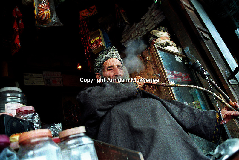 A shop owner smokes the traditional Kashmiri pipe called Jajeer at the market at world famous Dal Lake,Srinagar. Kashmir valley, india