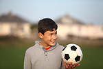 Boy with soccer ball outside in the golden hour near sunset