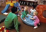 Berkeley, CA Caregiver interacting with children around one-year-old at infant day care