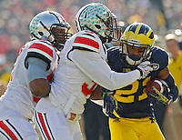 Ohio State Buckeyes defensive back Corey Brown (3) and Ohio State Buckeyes linebacker Joshua Perry (37) come together to tackle Michigan Wolverines wide receiver Jeremy Gallon (21) in the 4th quarter of their college football game at Michigan Stadium in Ann Arbor, Michigan on November 30, 2013.  (Dispatch photo by Kyle Robertson)