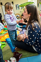 "A mother breastfeeding her baby at a drop-in breastfeeding support centre while talking to her older daughter.<br /> <br /> Image from the ""We Do It In Public"" documentary photography project collection: <br />  www.breastfeedinginpublic.co.uk<br /> <br /> Dorset, England, UK<br /> 17/04/2013"