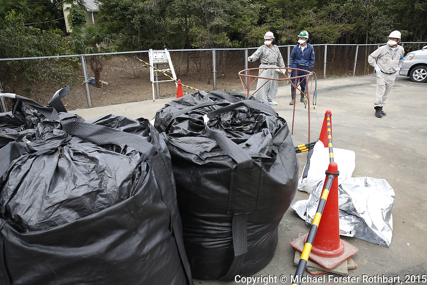 Ben Takeda, a Fukushima decontamination supervisor working for the Joint Venture in Tomioka, Japan, in the Fukushima Exclusion Zone, checks in with laborers working to decontaminate homes and commercial properties. Almost all developed properties in Tomioka are now getting cleaned or demolished four and a half years after the Fukushima Daiichi nuclear power plant disaster. Full caption to come.<br /> <br /> &copy; Michael Forster Rothbart Photography<br /> www.mfrphoto.com &bull; 607-267-4893<br /> 34 Spruce St, Oneonta, NY 13820<br /> 86 Three Mile Pond Rd, Vassalboro, ME 04989<br /> info@mfrphoto.com<br /> Photo by: Michael Forster Rothbart<br /> Date:  10/6/2015<br /> File#:  Canon &mdash; Canon EOS 5D Mark III digital camera frame B20592