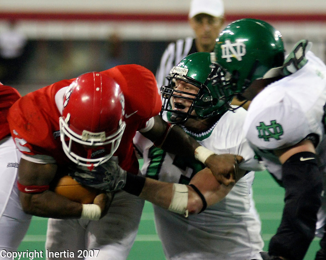Brett Holinka, #13 for the UND Fighting Sioux, makes a play on Matt Lee, #31 for the USD Coyotes, during a kickoff in the 4th quarter of Saturday's game.