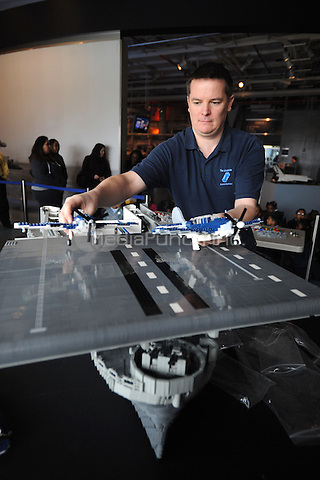 Artist Ed Diment assembles a 22-foot-long model USS Intrepid out of LEGO bricks at the Intrepid Sea, Air & Space Museum in New York City. April 15. 2011. Credit: Dennis Van Tine/MediaPunch