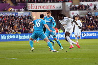 SWANSEA, WALES - FEBRUARY 07: Bafetimbi Gomis of Swansea (R) attempts to get past John O'Shea and Santiago Vergini of Sunderland during the Premier League match between Swansea City and Sunderland AFC at Liberty Stadium on February 7, 2015 in Swansea, Wales.